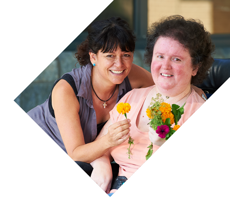 Two people enjoying time together holding colourful flowers.