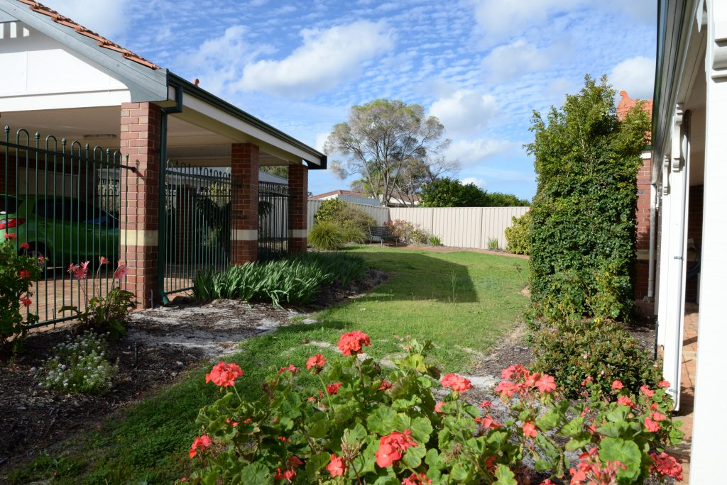 Side of red brick house and back garden with green grass and pink flowers